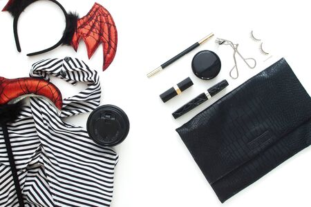 Creative flat lay of woman dress and accessories for Halloween party on white background.