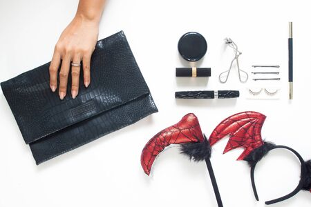 Creative flat lay of woman hand holding trendy purse with Halloween party accessories and cosmetics on white background. Beauty Halloween concept Фото со стока