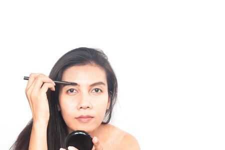Portrait of 40s Asian woman applying eyebrow. Make up and Beauty concept. Anti aging and surgery. Фото со стока