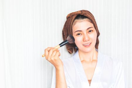 Facial Makeup. Beautiful Asian Female Model Putting Blush With Cosmetic Brush. Portrait Of Attractive Healthy 30+ Year Old Woman With Pure Clean Skin And Natural Make-Up. Beauty Concept.