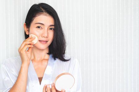 Facial Makeup. Beautiful Asian woman applying powder on face