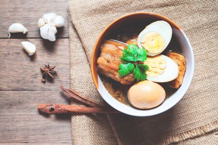 Stewed eggs and pork or eggs and pork in brown sauce in bowl with spices on wooden table. Top view