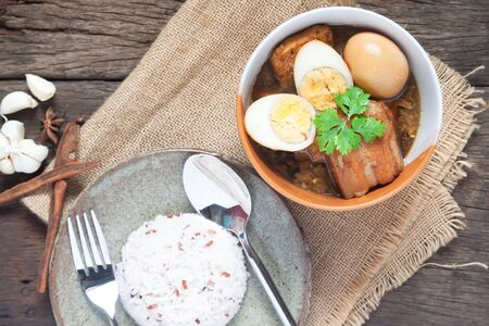 Stewed eggs and pork or eggs and pork in brown sauce in bowl with rice on wooden table. Top view