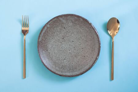 Empty plate, Table setting. Ceramic plate, spoon and fork on blue colour background Фото со стока