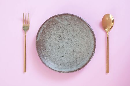 Empty plate, Table setting. Ceramic plate, spoon and fork on pink pastel colour background