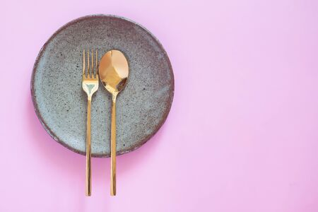 Table setting, Ceramic dishware, spoon and fork on pink pastel color background Фото со стока