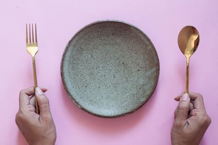 Top view of table, woman hands holding fork and spoon with empty plate on pink background