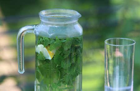 lemon balm: lemon balm tea in a glass jar and a glass, standing outdoors on a terrace Stock Photo