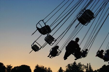 silhouettes of a father and children in a swing carousel, at sunset