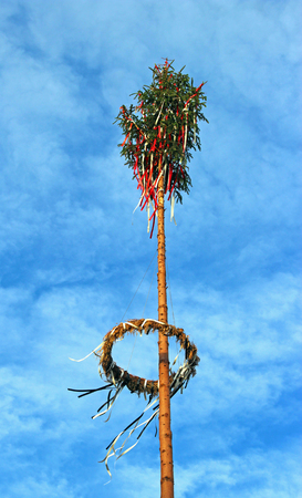 decorated may pole against a blue sky