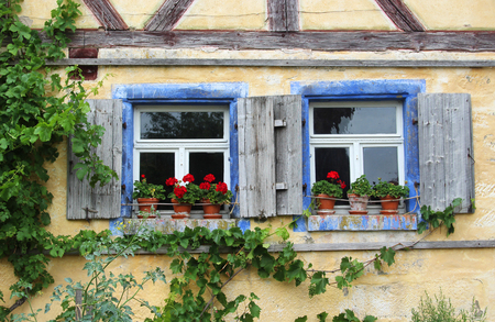 Two old windows with shutters and red geraniums in a half-timbered house Stockfoto