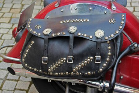 black leather bag with lots of rivets on an old red motorcycle, standing on pavement