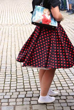woman dressed in sixties style with petticoat, spotted skirt and Marilyn-Monroe-Bag, side view, on pavement Stock Photo