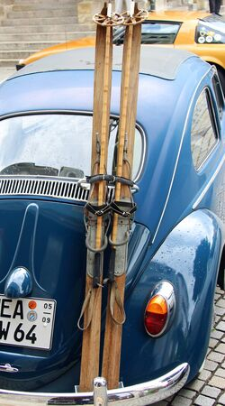 a pair of wooden skis and ski sticks strapped on the back of an oldtimer car Redakční