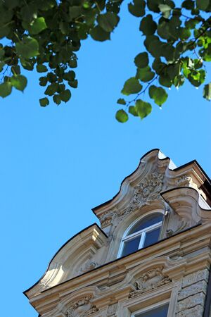 decorative gable of a baroque house with window, blue sky, green leaves Stock Photo