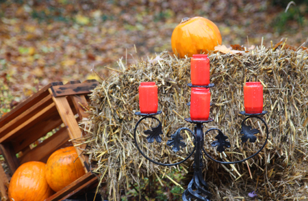 chandelier: Halloween decoration outdoors, chandelier with red grave light and pumpkins on straw bale