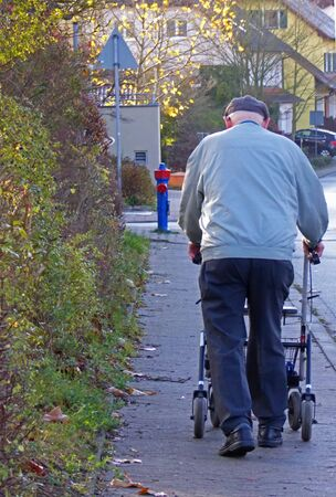 rear view of a senior man with a rollator walking on a sidewalk Stock Photo