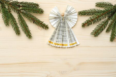 Christmas background, angel folded with paperfrom a church songbook and spruce branches