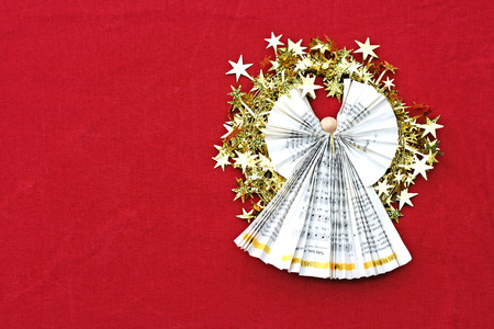 angel folded of paper with a wreath of goden stars on red cloth Stock Photo