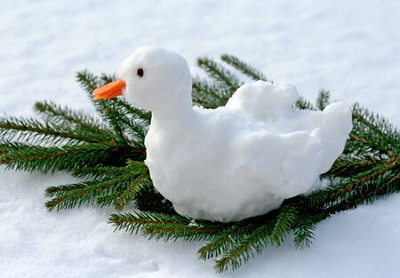 Christmas goose made of snow sitting on a fir branch, sunlight Stock Photo