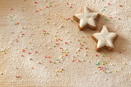 Christmas background with cinnamon stars, sprinkles and sugar as snow