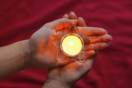 Hands of a woman holding a lit tea light in star shape, top view, red background