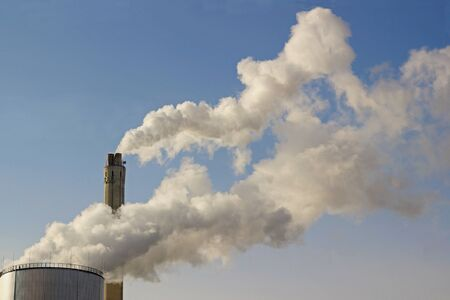 steam clouds from industry chimneys in front of blue sky Imagens