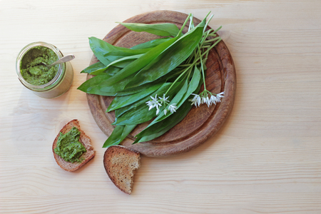 a glass with green wild garlic pesto and fresh garlic leaves on a cutting board