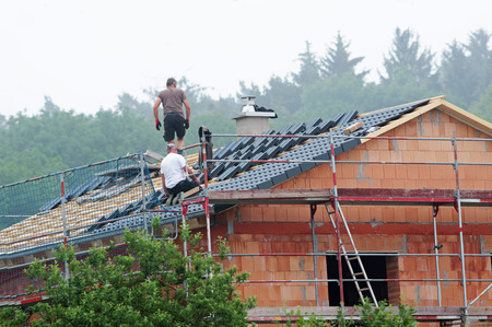 two roofers tiling the roof of a shell construction near a forest Stock Photo