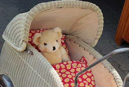 Flea market, teddy bear lying in an old wicker pram