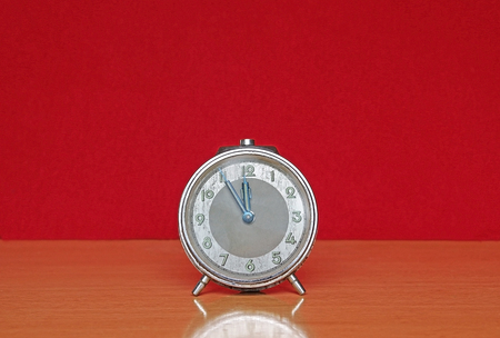 Five minutes to midnight on a retro alarm clock, isolated on a red background