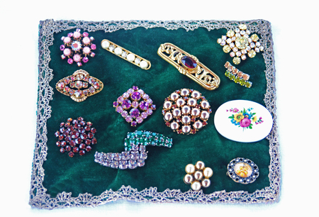 various vintage brooches on a green velvet cloth with a lace border Banque d'images - 105907996