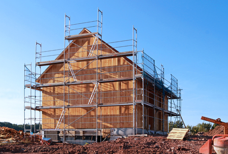 wooden house in construction, with scaffold, in front of blue sky Zdjęcie Seryjne