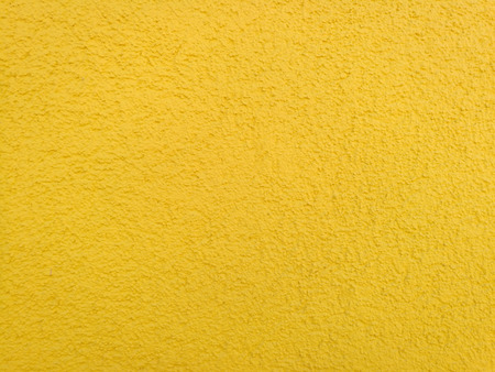 yellow background, wall with roughcast in a warm tone, closeup Stock Photo