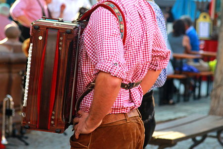 man with an accordion, red checkered shirt and bavarian leather trousers, beer garden in background Standard-Bild
