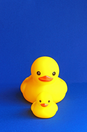 small rubber duck and large rubber duck swimming one after another, blue background
