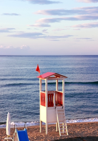 sunset at an italian beach with a red and white lifeguard watchtower Foto de archivo