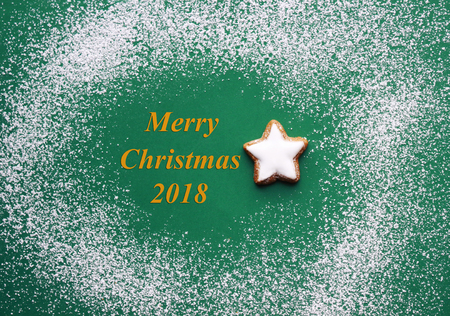 Merry Christmas 2018, green greeting card with powdered sugar as snow and a  star cookie