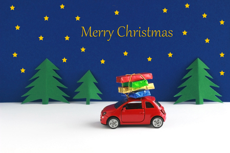 Merry christmas, greeting card with a red car, gift parcels on its roof, driving through a winter landscape at night Banco de Imagens