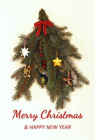 retro christmas and new year card with beautiful decorated  spruce branches with stars and a red ribbon