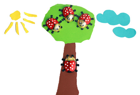tree with three ladybugs, fourth ladybug creeping up the tree trunk