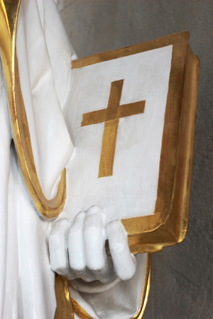 close-up of a Holy bible, held by a saint, part of a historic sculpture