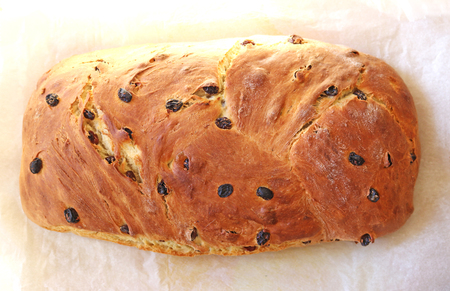 gold brown baked Easter bread or Easter twist coming out of the oven, lying on baking paper