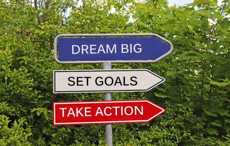 Three signs with arrow pointing in the same direction, with the message dream big, set goals, take action