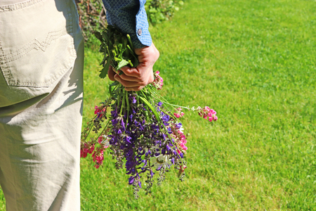 rear view of a man in a garden, holding a bunch of multi colored wildflowers Stock Photo