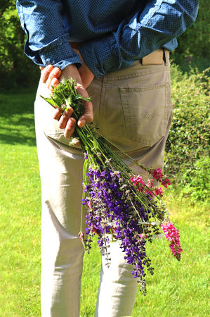 rear view of a man in a garden, holding a bunch of multi colored wildflowers behind his back