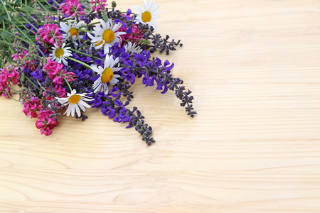 bunch of wildflowers lying on a wooden table, rural background with copy space Stock Photo