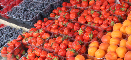 strawberries, blueberries, raspberries and apricots presented at a market Stock Photo