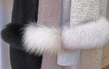 sleeves of knitted jackets with faux fur hanging in a store Banco de Imagens