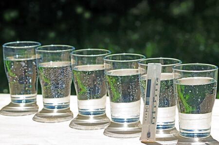 row of glasses with sparkling water and a thermometer displaying more than 30 degrees Celsius standing on a table in a garden